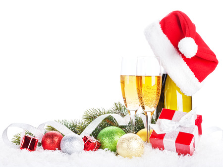 wine background: Champagne, christmas decor and santa hat over snow and fir tree with copy space