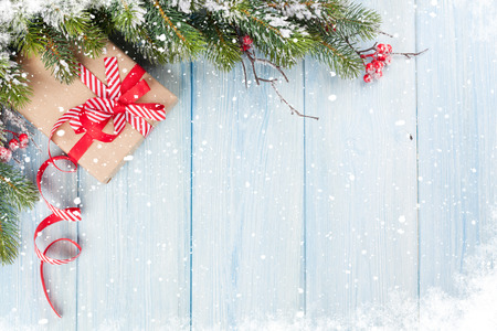 fir: Christmas wooden background with snow fir tree and gift box. View with copy space