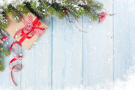 Kerst houten achtergrond met sneeuw dennenboom en geschenkdoos. Weergave met kopie ruimte Stockfoto