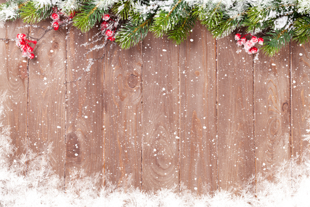 table: Christmas wooden background with snow fir tree. View with copy space