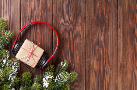 retro music: Christmas gift box with headphones and tree branch. Top view with copy space