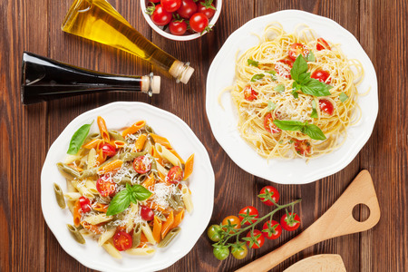 two on top: Spaghetti and penne pasta with tomatoes and basil on wooden table. Top view