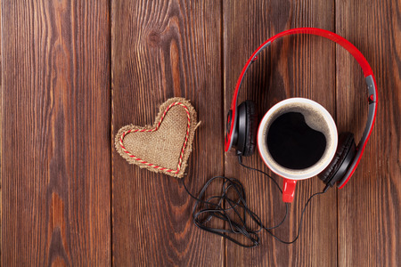 headphones: Heart toy with headphones and coffee cup on wooden table with copy space. Valentines day concept.