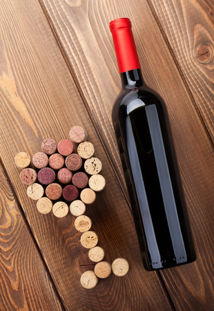 Red wine bottle and glass shaped corks. View from above over rustic wooden table background Stock Photo