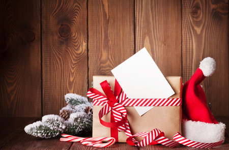 card: Christmas gift box and santa hat on wooden table