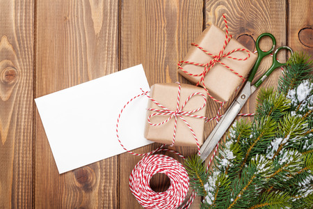 christmas wrapping: Christmas presents wrapping and snow fir tree over wooden table background with greeting card copy space