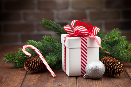 christmas gift box: Christmas gift box and fir tree branch on wooden table