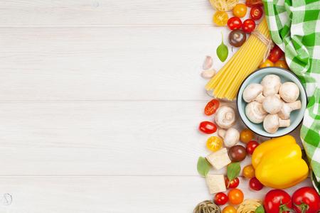 comida italiana: Ingredientes para cocinar la comida italiana. Pasta, verduras, especias. Vista superior con espacio de copia Foto de archivo