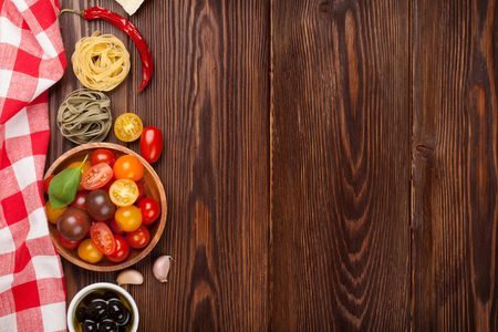 rustic table: Italian food cooking ingredients. Pasta, vegetables, spices. Top view with copy space