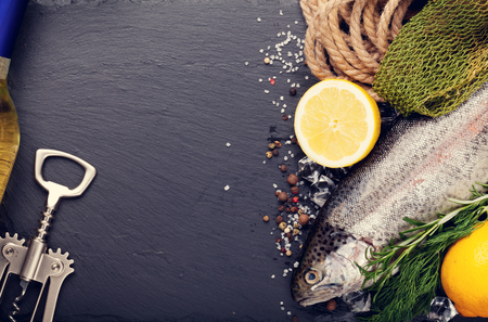 rainbow fish: Fresh raw rainbow trout fish with spices and white wine on black stone with copy space. Toned Stock Photo