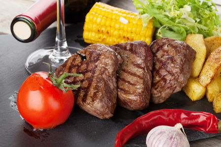 food and wine: Steak with grilled potato, corn, salad and red wine closeup