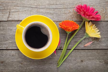 Tasse Kaffee und Gerbera Blumen auf Holztisch