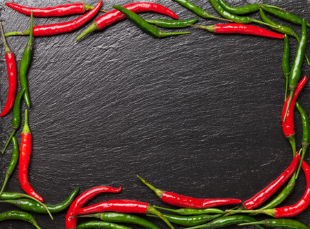 Chili peppers on black stone table with copy space