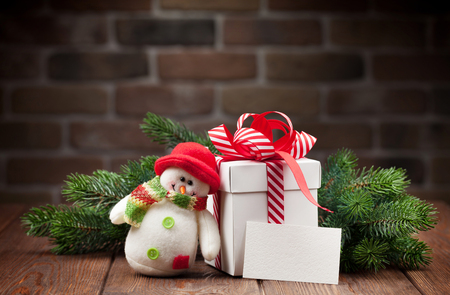 holiday home: Christmas gift box, snowman toy, greeting card and fir tree branch on wooden table