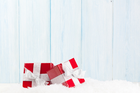 christmas decorations: Christmas gift boxes in snow and wooden background with copy space