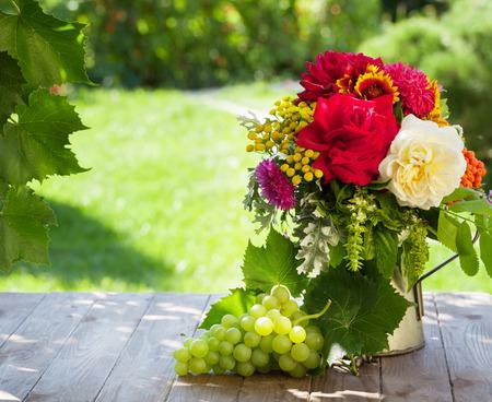 Mazzo di fiori da giardino e uva sul tavolo di legno. Visualizza con copia spazio