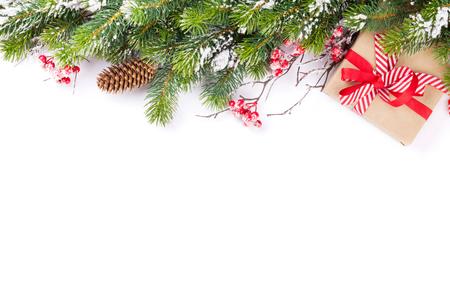 vacaciones: Rama de un árbol de Navidad con nieve y caja de regalo. Aislado en fondo blanco con espacio de copia