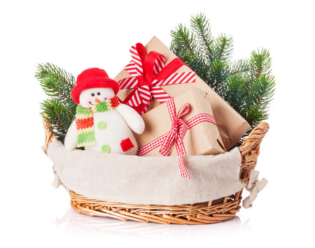 the basket: Christmas gift boxes, snowman toy, fir tree in basket. Isolated on white background Stock Photo