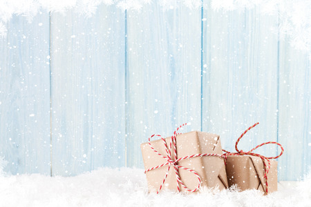 traditional gifts: Christmas gift boxes in snow and wooden background with copy space