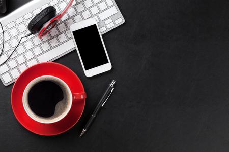 オフィス コーヒー カップ、コンピューター、スマート フォン、ヘッドフォン付き革デスク テーブル。コピー スペース平面図 写真素材