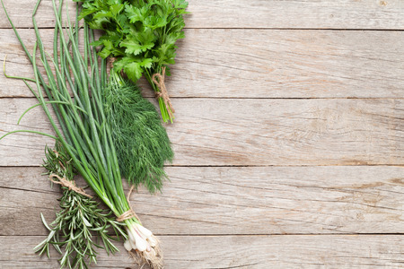 spring onion: Fresh garden herbs on wooden table. Top view with copy space