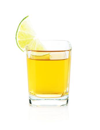 alimentos y bebidas: Shot de tequila de oro con una rodaja de lim�n. Aislado en el fondo blanco
