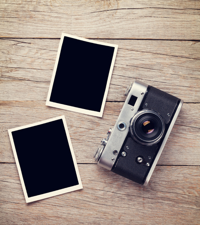 vintage retro frame: Vintage film camera and two blank photo frames on wooden table. Top view Stock Photo