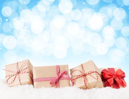 cajas navideñas: Cajas de regalo de Navidad en la nieve con el fondo bokeh de espacio de la copia Foto de archivo