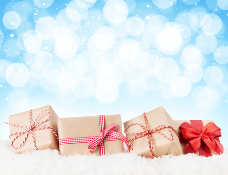 Christmas gift boxes in snow with bokeh background for copy space Stockfoto