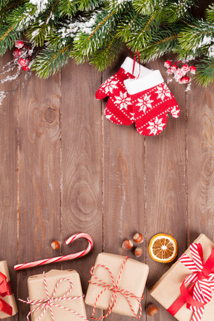candy border: Christmas wooden background with snow fir tree and gift boxes. View with copy space Stock Photo