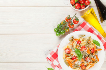 utensils: Colorful penne pasta with tomatoes and basil on wooden table. Top view with copy space