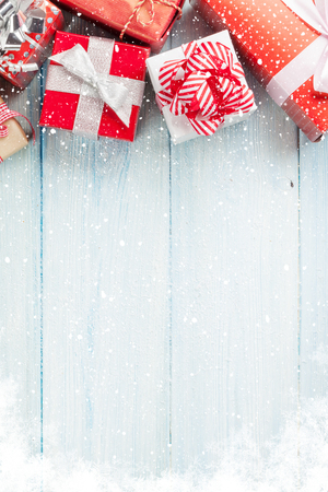 red white blue: Christmas gift boxes on wooden table with snow. Top view with copy space