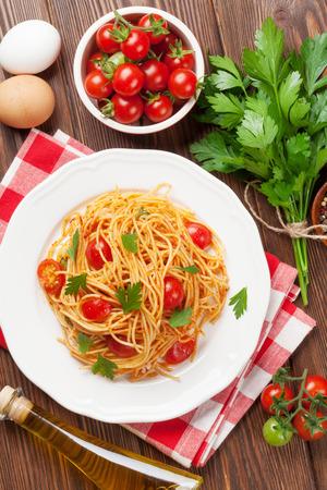スパゲッティ パスタ トマトとパセリの木製のテーブルの上。トップ ビュー 写真素材