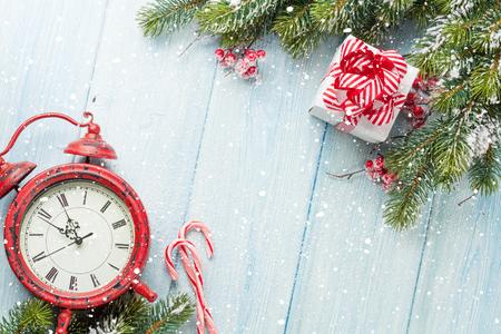 cajas navide�as: caja de regalo de la Navidad, despertador, bast�n de caramelo y rama de abeto de la mesa de madera. Vista superior Foto de archivo