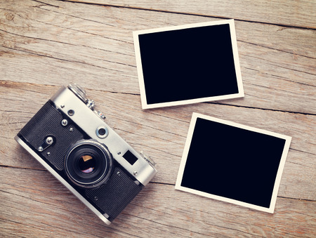 grunge border: Vintage film camera and two blank photo frames on wooden table. Top view Stock Photo