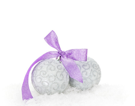 christmas baubles: Christmas baubles and purple ribbon over snow. Isolated on white background with copy space