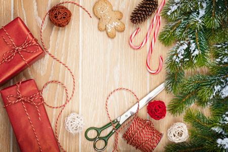 クリスマス プレゼント包装や雪モミの木木製テーブル背景にコピー スペースを持つ