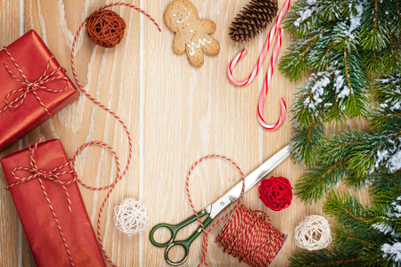 wrappings: Christmas presents wrapping and snow fir tree over wooden table background with copy space