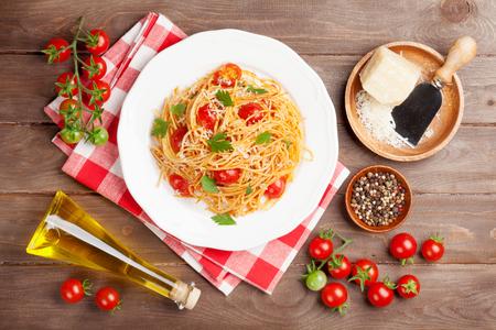 Spaghetti pasta met tomaten en peterselie op houten tafel. Bovenaanzicht