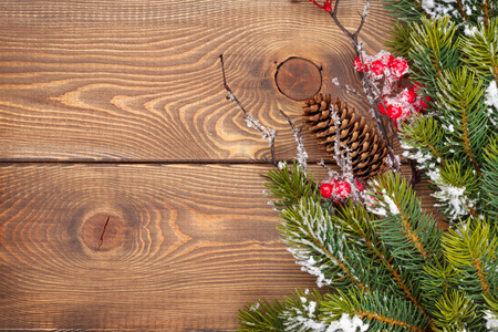 snow cone: Christmas wooden background with snow fir tree and holly berry