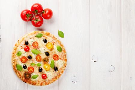 pizza: Pizza italiana con queso, tomate, aceitunas y albahaca sobre la mesa de madera. Vista superior con espacio de copia Foto de archivo