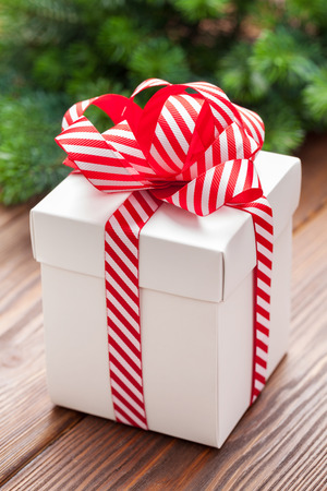 gift bow: Christmas gift box and fir tree branch on wooden table