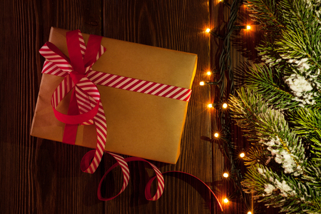 wooden box: Christmas gift box, tree branch and lights on wooden background Stock Photo
