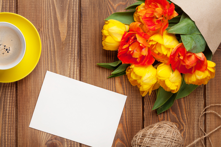 photo paper: Colorful tulips bouquet, blank greeting card and coffee cup on wooden table Stock Photo