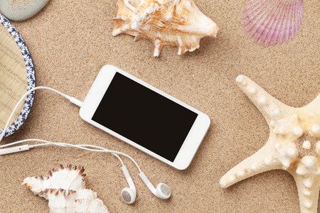 vacation destinations: Smartphone on sea sand with starfish and shells. Top view with copy space Stock Photo