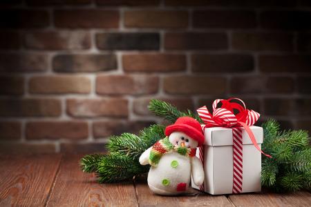 juguetes: Caja de regalo de la Navidad, juguete mu�eco de nieve y la rama de abeto en mesa de madera. Ver con copia espacio