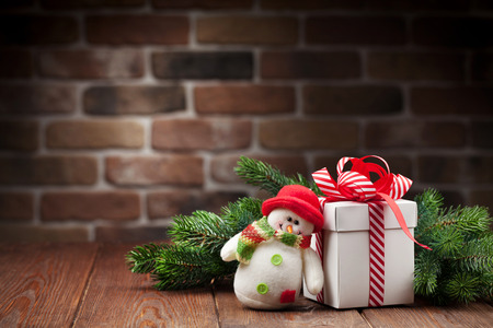 snowman: Christmas gift box, snowman toy and fir tree branch on wooden table. View with copy space Stock Photo