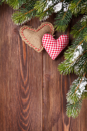 heart: Christmas tree branch with snow and heart toys on wooden table. Top view with copy space