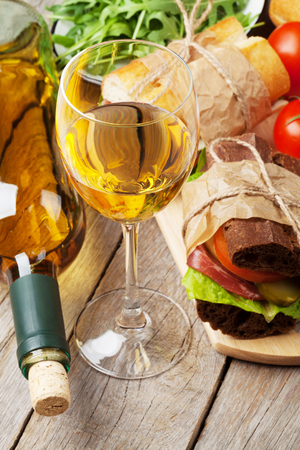 sandwiches: White wine glass and sandwiches on wooden table