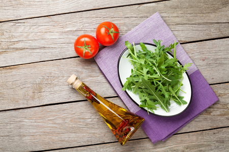 roquette: Arugula salad, tomatoes and olive oil bottle over rustic wooden table